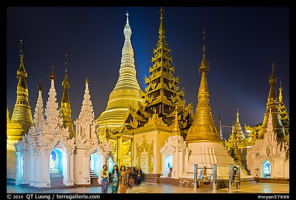 Women walking, stupas, shrines, and Main Stupa at night, Shwedagon Pagoda. Yangon, Myanmar (color)