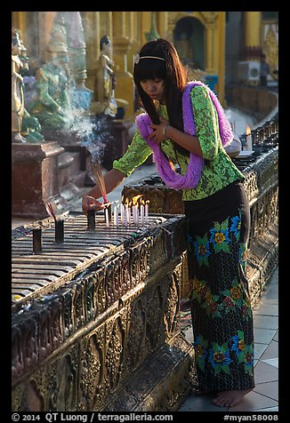Woman lighting candles, Shwedagon Pagoda. Yangon, Myanmar (color)