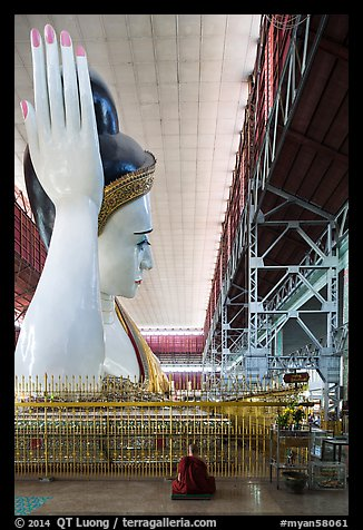 Monk and reclining Buddha statue housed in large metal shed, Kyauk Htat Gyi Pagoda. Yangon, Myanmar (color)