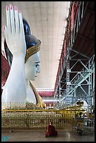 Monk and reclining Buddha statue housed in large metal shed, Kyauk Htat Gyi Pagoda. Yangon, Myanmar ( color)