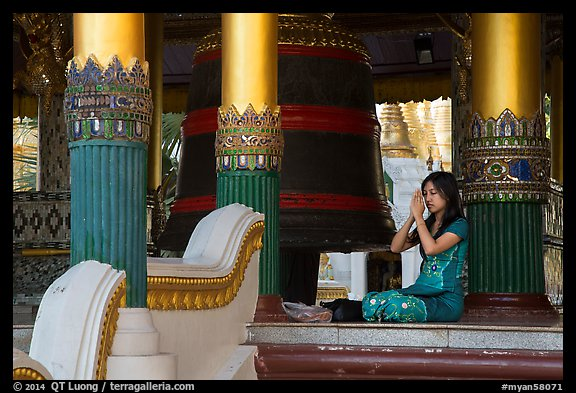 Woman praying next to bell, Shwedagon Pagoda. Yangon, Myanmar (color)