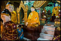 Woman and monk in pavillion surrounded by Buddha statues. Yangon, Myanmar ( color)