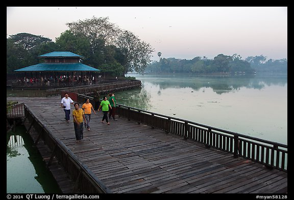 People walking for exercise at dawn, Kandawgyi Lake Park. Yangon, Myanmar (color)
