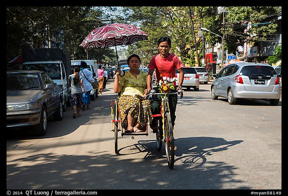 Woman holding unbrella against sun while riding Trishaw. Yangon, Myanmar (color)