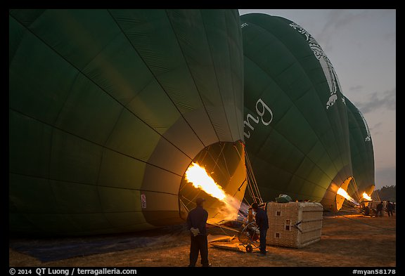 Crew inflates hot air balloons with propane burners. Bagan, Myanmar (color)
