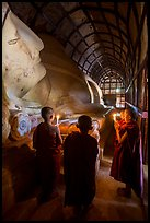 Novices standing with candles next to Shin Bin Thal Yaung reclining Budddha. Bagan, Myanmar ( color)