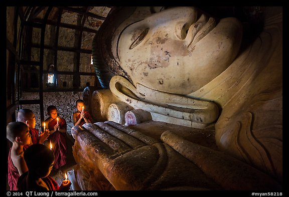Young monks with candles worship Shin Bin Thal Yaung reclining Budddha. Bagan, Myanmar (color)