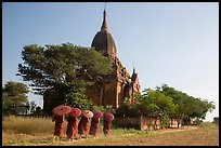 Five novices with red umbrellas walking below temple. Bagan, Myanmar ( color)