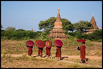 Buddhist Novices with red sun umbrellas on path near old stupas. Bagan, Myanmar ( color)