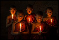 Young buddhist monks holding candles with eyes closed. Bagan, Myanmar ( color)