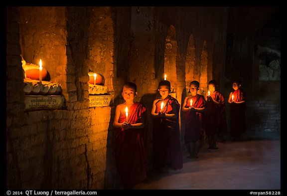Buddhist novices in temple illuminated with candles. Bagan, Myanmar (color)