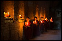Buddhist novices in temple illuminated with candles. Bagan, Myanmar ( color)