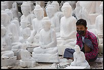 Man working amongst many  buddha statues on Marble street workshop. Mandalay, Myanmar ( color)