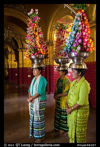 Women carry elaborate flower offerings on their head, Mahamuni Pagoda. Mandalay, Myanmar (color)