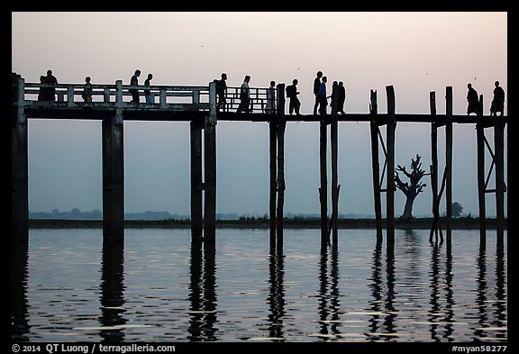 U Bein Bridge with monks and visitors strolling at dusk. Amarapura, Myanmar (color)