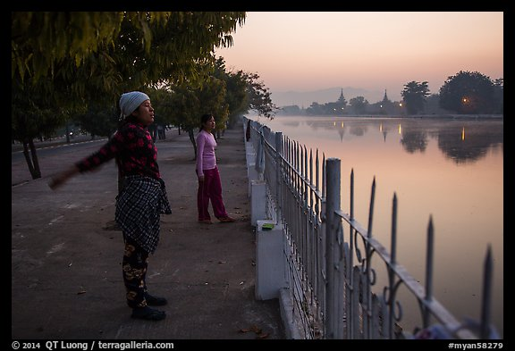 Women exercising next to Mandalay Fort at dawn. Mandalay, Myanmar (color)