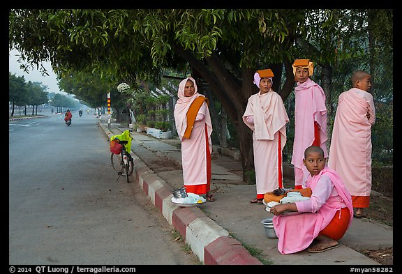 Nuns waiting for ride on sidewalk. Mandalay, Myanmar (color)