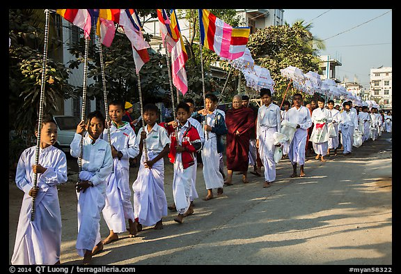 Children carry Buddhist flags ahead of alms procession. Mandalay, Myanmar (color)