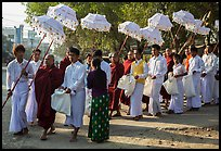 Umbrella bearer, Monks, and donation holders in alms procession. Mandalay, Myanmar ( color)