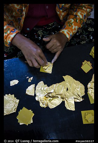 Close-up of hands separating gold leaves. Mandalay, Myanmar (color)