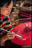 Woman painting the paper sun umbrellas carried by the monks. Pindaya, Myanmar ( color)
