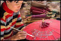 Woman painting the red umbrellas carried by the monks. Pindaya, Myanmar ( color)