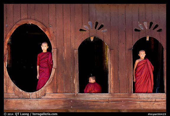 Buddhist monks looking through windows of Shweyanpyay Monastery, Nyaung Shwe. Inle Lake, Myanmar (color)