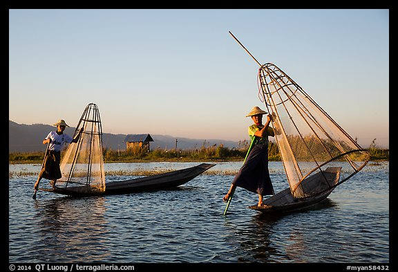 Intha fishermen row with leg and hold conical baskets. Inle Lake, Myanmar (color)