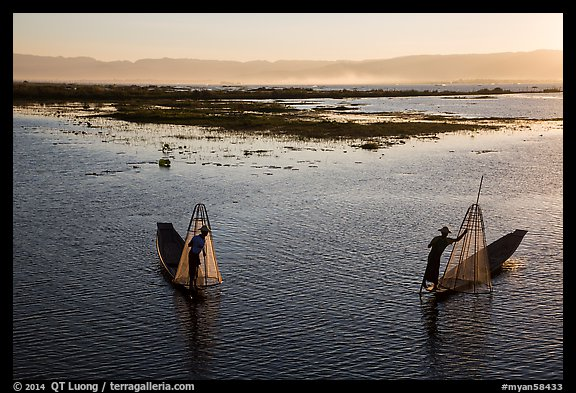 Intha fishermen row with backlit conical nets. Inle Lake, Myanmar (color)