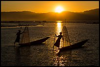 Intha fishermen row with leg with setting sun. Inle Lake, Myanmar ( color)