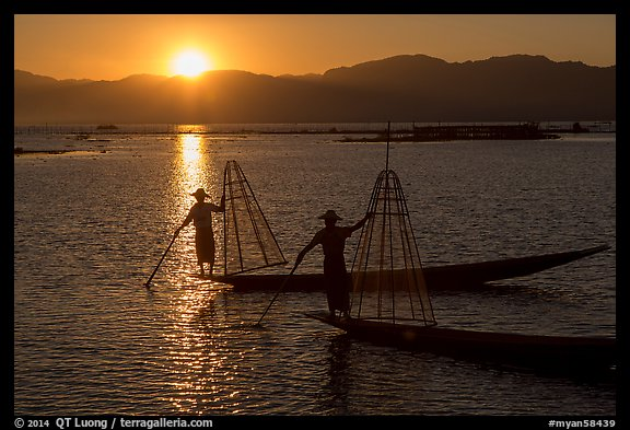Intha fishermen on long flat-bottomed boats at sunset. Inle Lake, Myanmar (color)