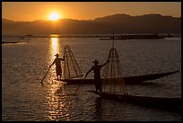 Intha fishermen on long flat-bottomed boats at sunset. Inle Lake, Myanmar ( color)