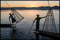 Intha fishermen lifting traditional conical net at sunset. Inle Lake, Myanmar ( color)