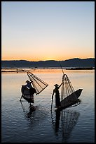 Intha fishermen lifting conical basket net at sunset. Inle Lake, Myanmar ( color)