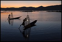 Leg-rowing Intha fishermen with lanterns at dusk. Inle Lake, Myanmar ( color)