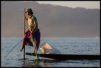 Fisherman pulling up net while leg-rowing. Inle Lake, Myanmar ( color)