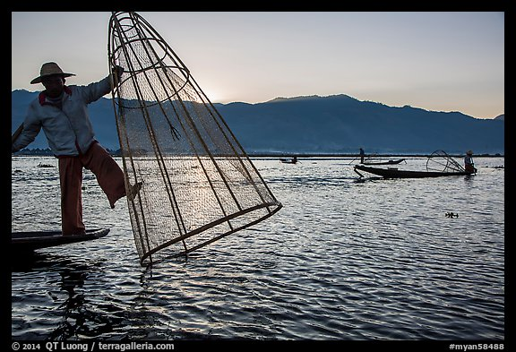 Intha fisherman standing on boat stern to lift net basket. Inle Lake, Myanmar (color)