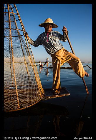 Intha fisherman prepares to release conical basket. Inle Lake, Myanmar (color)