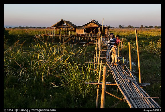 Family walking out of stilt house on precarious bridge. Inle Lake, Myanmar (color)