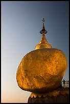 Pilgrim prays to the gleaming Golden Rock at sunset. Kyaiktiyo, Myanmar ( color)