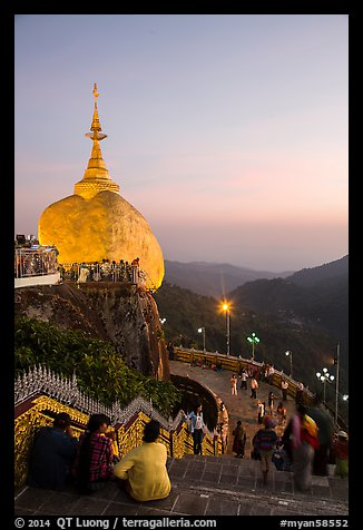 Pilgrims look at the Golden Rock from lower platform at sunset. Kyaiktiyo, Myanmar (color)