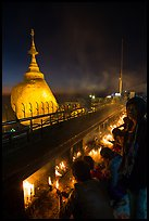 Pilgrims light up candles behind the Golden Rock at dusk. Kyaiktiyo, Myanmar ( color)