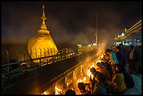 Pilgrims pray with candles behind the Golden Rock. Kyaiktiyo, Myanmar ( color)