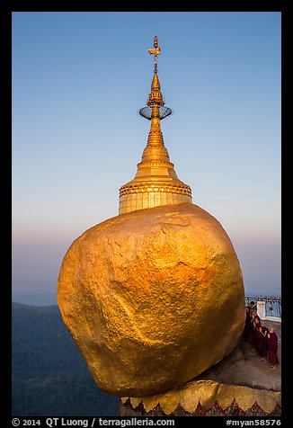 Monks standing in prayer near the Golden rock at sunrise. Kyaiktiyo, Myanmar (color)
