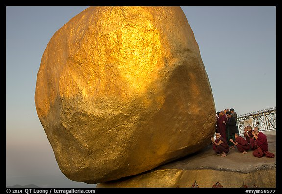 Monks praying at the Golden Rock balancing boulder. Kyaiktiyo, Myanmar (color)