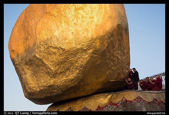 Monks kneeling in prayer at the Golden Rock. Kyaiktiyo, Myanmar (color)
