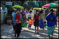 Women walk with platers of food on their heads. Kyaiktiyo, Myanmar ( color)