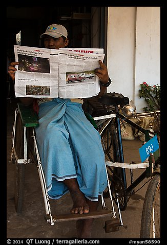 Cyclo driver reading newspaper with picture of QT Luong tour group. Bago, Myanmar (color)