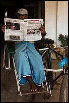 Cyclo driver reading newspaper with picture of QT Luong tour group. Bago, Myanmar ( color)