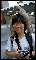 Monkeys climb on a tourist, San Phra Kan. Lopburi, Thailand (color)